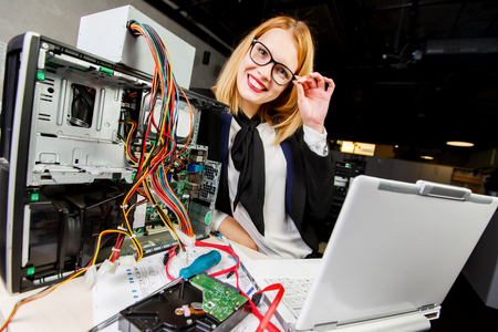 Image of woman in glasses at table with broken processor and laptop 写真素材