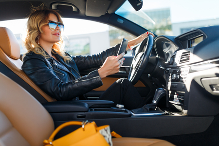 Image of blonde woman in black glasses with cell phone sitting in car