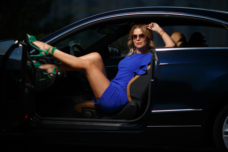Image of woman in purple dress sitting in black car