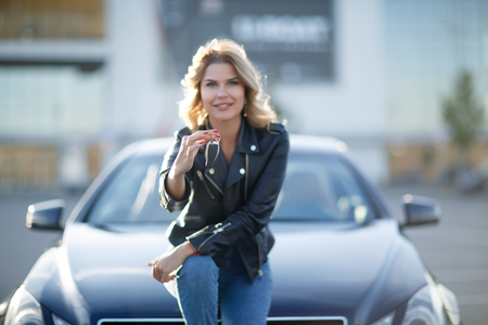Image of young blonde with keys sitting on hood of black car