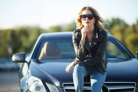 Photo of young woman in sunglasses sitting on hood of black car