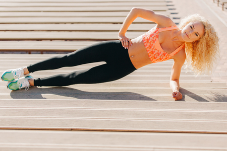 Picture of sports woman exercising among benches in summer day 版權商用圖片
