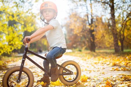 Photo of boy in helmet on running bike in autumn park