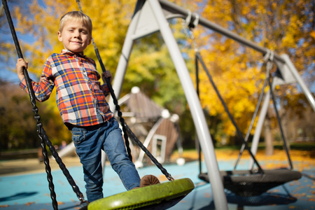 Photo of boy swinging on swing on autumn afternoon