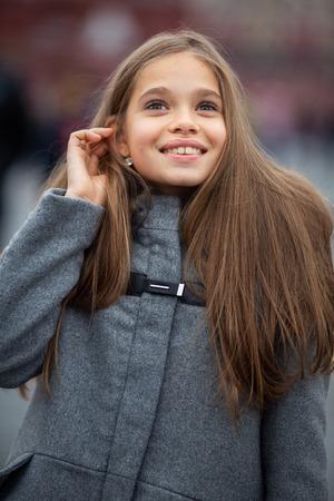 Photo of smiling girl in gray coat