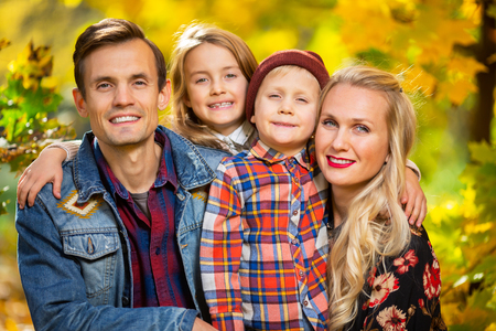 Photo of smiling family with children on walk in autumn park