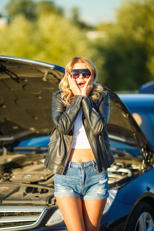 Photo of young upset woman near broken car with open hood