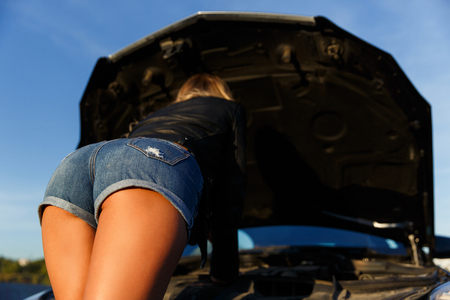 Image of back of young girl in short shorts mending black car in summer day
