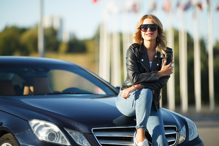 Image of young woman in sunglasses sitting on hood of black car
