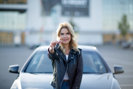 Picture of young blonde with keys sitting on hood of black car