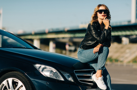 Image of young blonde woman in sunglasses sitting on hood of black car
