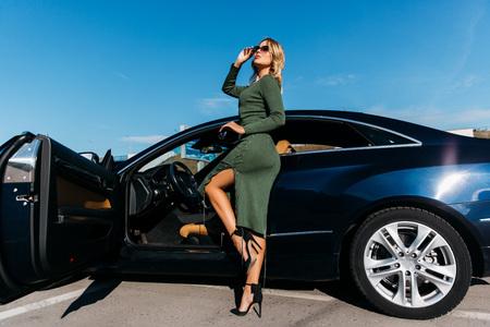 Photo de jeune blonde avec des clés dans des lunettes de soleil en robe longue debout près d'une voiture noire avec porte ouverte Banque d'images