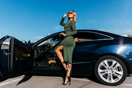 Photo of young blonde with keys in sunglasses in long dress standing near black car with open door