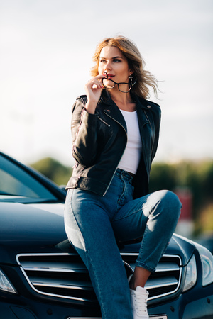 Portrait of young blonde with glasses in hands sitting on hood of black car