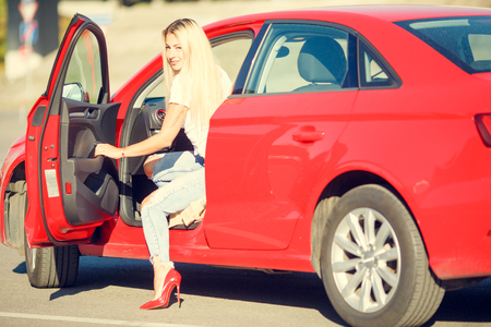 Image of young blonde leaving red car Stock Photo