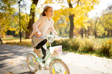 Image of girl in skirt riding bike in autumn park Reklamní fotografie