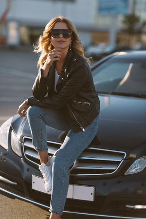 Photo of young blonde girl in sunglasses sitting on hood of black car