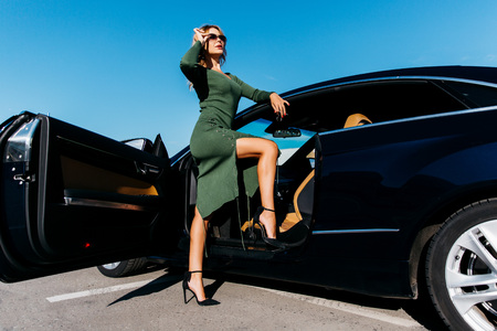 Photo of sexy blonde with keys in sunglasses in long dress standing near black car with open door