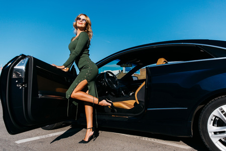 Photo of sexy blonde in sunglasses in long dress standing near black car with open door Stock Photo
