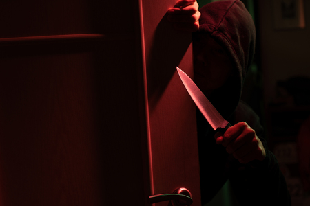 Picture of killer with knife and in hood in dark apartment with red light 版權商用圖片