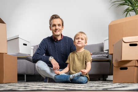 Image of father and boy sitting on floor among cardboard boxes