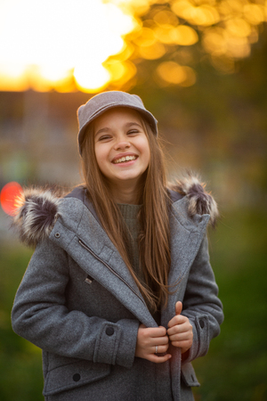 Photo of girl in gray hat and coat on blurred background at city