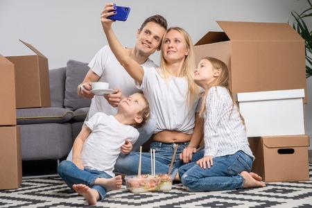 Image of man, children and women taking selfie sitting on floor among cardboard boxes