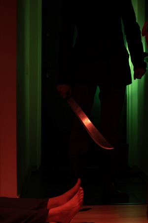 Photo of thief with machete and man lying on floor in dark apartment