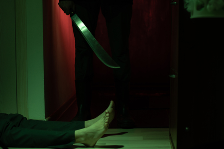 Picture of thief with machete and man lying on floor in dark apartment Stock Photo - 113885560