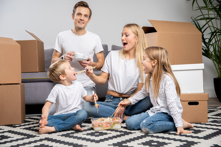 Photo of happy couple with children eating rice with shrimps sitting on floor among cardboard boxes