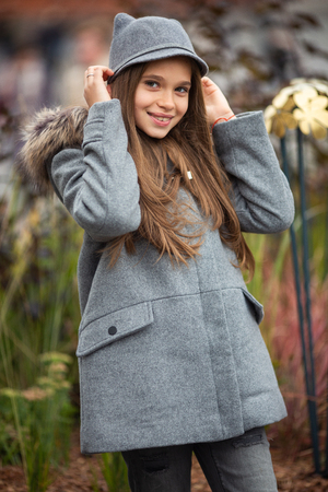 Photo of smiling girl in gray hat and coat