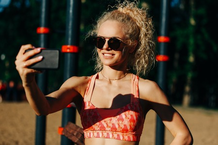 Photo of smiling sports woman wearing sunglasses doing selfie in Stock Photo