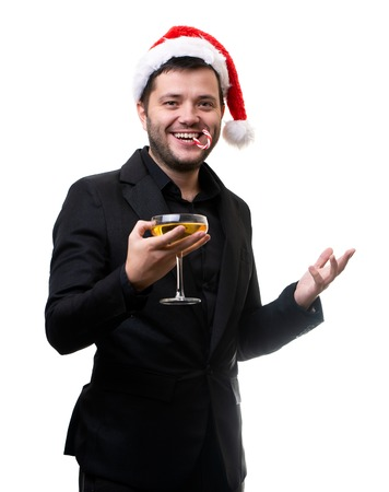 Photo of man in Santas cap, with caramel cane in mouth, with glass of champagne in hands