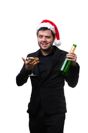 Image of man in Santas cap, with caramel cane in mouth, with glass of champagne, bottle in hands . Stock Photo