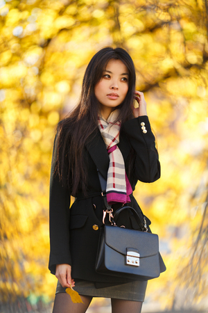Photo of eastern girl with flour, in black coat in autumn forest
