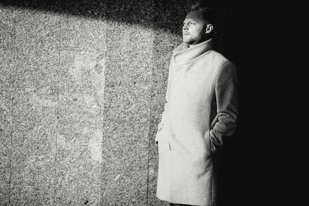 Black and white photo of man in coat walking near wall Banque d'images