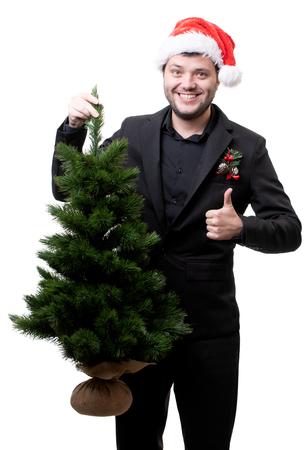 Photo of happy man in Santa hat with Christmas tree Stock Photo