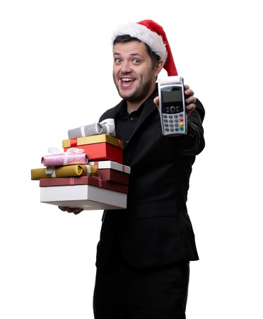 Photo of happy man in santa hat with boxes with gifts with terminal in hands Stock Photo
