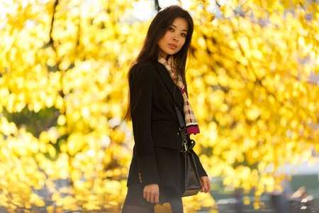 Photo of oriental girl with flour, in black coat in autumn forest
