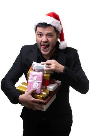 Photo of brunet in santa hat with boxes with gifts in hands on blank white background