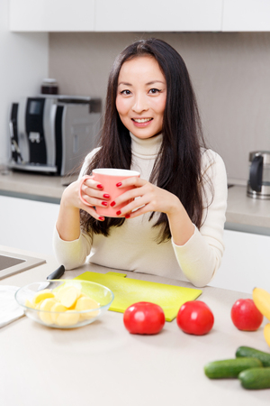 Photo of young brunette with mug in hands standing at table with vegetables and fruits