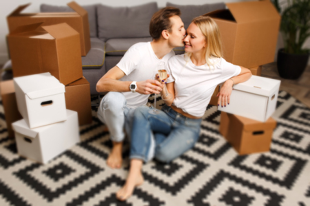 Image of young couple with wine glasses sitting on floor among cardboard boxes