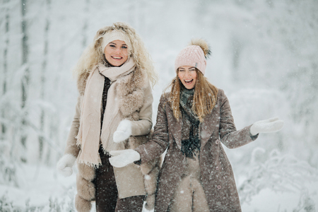 Photo of two blondes throwing snow on walk in winter forest Stock Photo