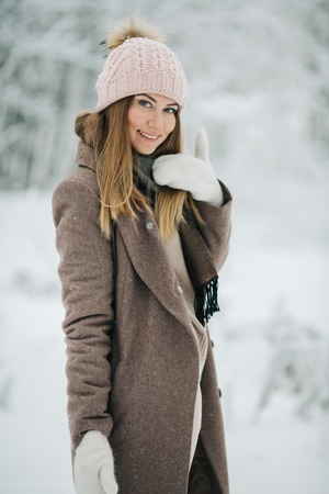 Image of happy blonde girl in hat on walk in winter forest