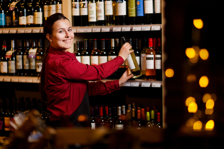 Picture of smiling woman with bottle in her hands in wine shop