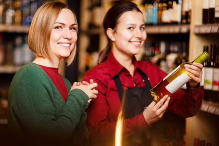 Photo of two smiling women with bottle of wine in store on background of shelves Stock fotó
