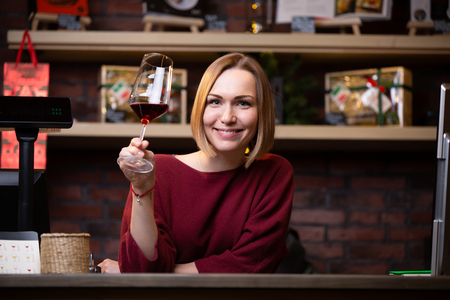 Photo of happy woman seller with wine glass standing behind cash register