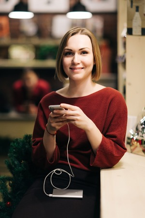 Photo of blonde seller with phone in hands, in black apron on blurred background. Reklamní fotografie