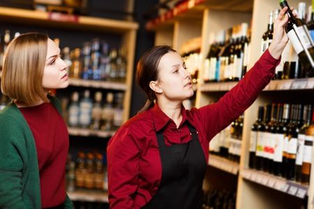 Photo of seller and buyer on blurred background of racks with bottles of wine