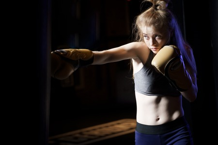 Portrait of girl boxer training near bag, ring in gym. 免版税图像